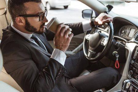 handsome driver in suit driving car and drinking coffee in paper cup