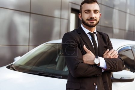 Photo for Handsome smiling businessman standing with crossed arms near car - Royalty Free Image