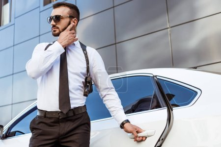 Handsome security guard listening message with security earpiece on street and opening car