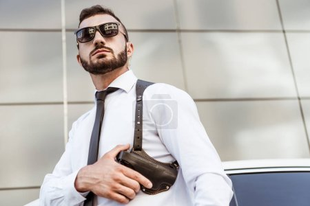 low angle view of handsome security guard in sunglasses touching gun and looking away