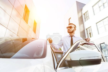 handsome driver in sunglasses standing near open car on street during sunset