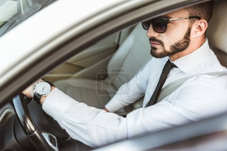 Photo for Side view of handsome driver in sunglasses driving car - Royalty Free Image