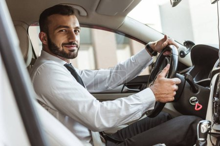 Photo for Smiling handsome driver holding steering wheel and looking at camera in car - Royalty Free Image