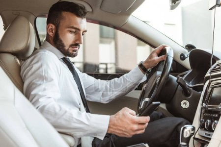 handsome driver in shirt driving car and looking at smartphone