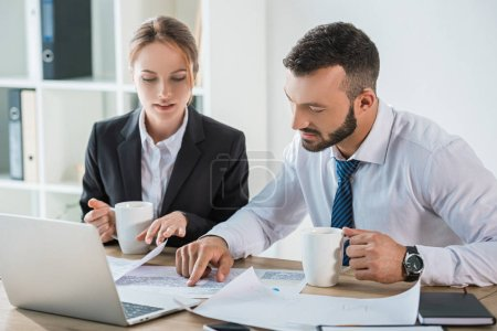 Photo for Financiers working with documents during coffee break in office - Royalty Free Image
