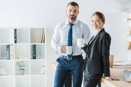 cheerful accountants holding cups with coffee and looking at camera in office