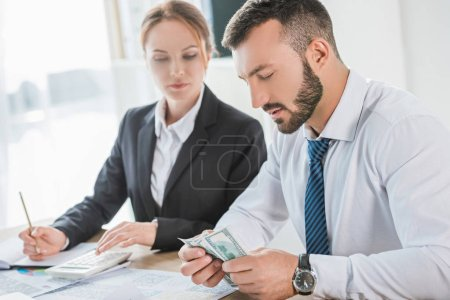 accountants counting dollar banknotes in office