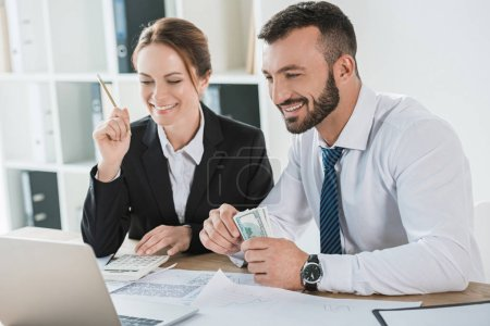 smiling financiers counting money and looking at laptop in office