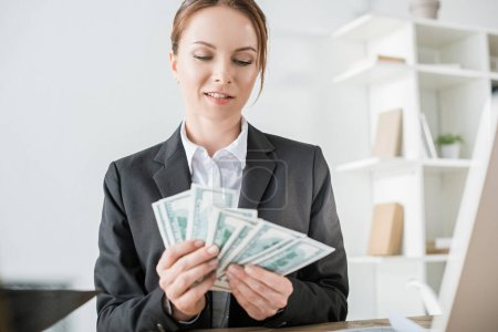 smiling financier counting cash in office