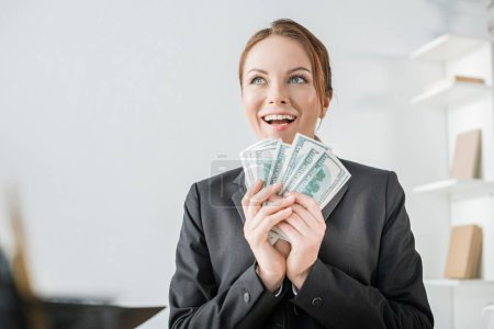 happy financier holding dollar banknotes in office