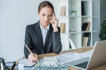 thoughtful financier looking at calculator in office