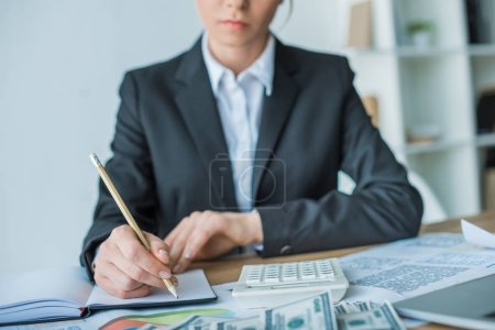 cropped image of financier writing something to notebook in office