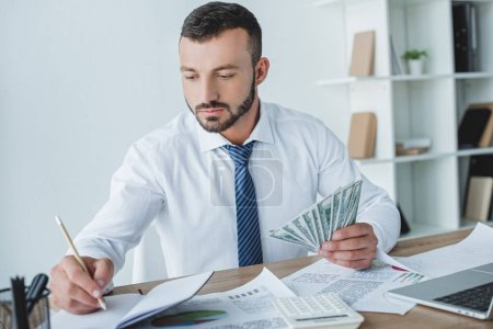handsome business adviser counting money in office and writing something to notebook