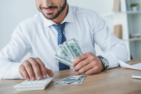 cropped image of business adviser counting money with calculator in office