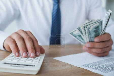 cropped image of financier counting money with calculator in office