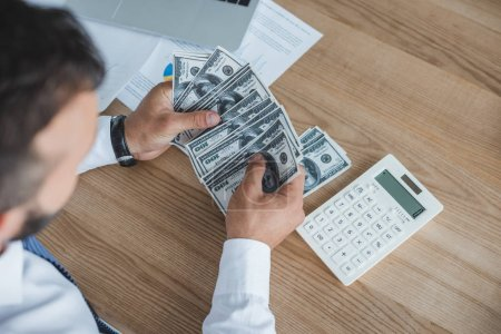 cropped image of financier counting cash with calculator in office