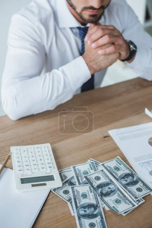 cropped image of pensive business adviser sitting at table in office