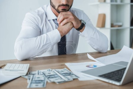 cropped image of pensive financier sitting at table in office