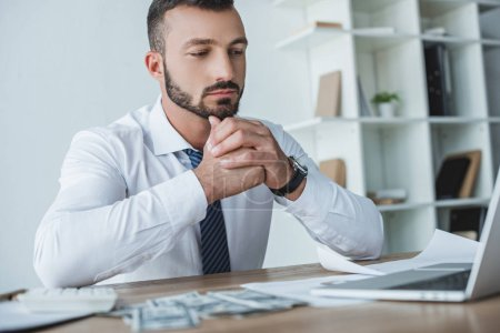 pensive financier sitting at table in office and looking at laptop