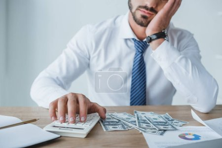 Photo for Cropped image of tired financier counting money with calculator in office - Royalty Free Image