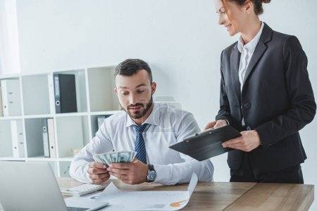 attractive financier showing clipboard to colleague in office