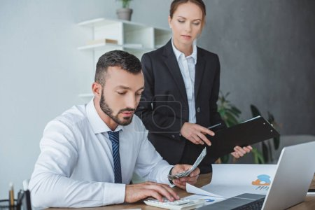 financier counting money in office, colleague standing with clipboard