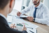 cropped image of financiers working at table in office