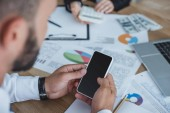 cropped image of financier using smartphone at table in office