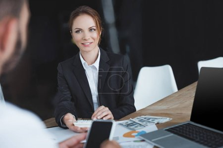 financiers looking at each other and holding smartphone and calculator in office