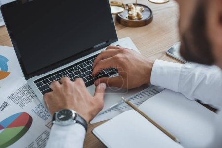 cropped image of business adviser working with laptop at table in office