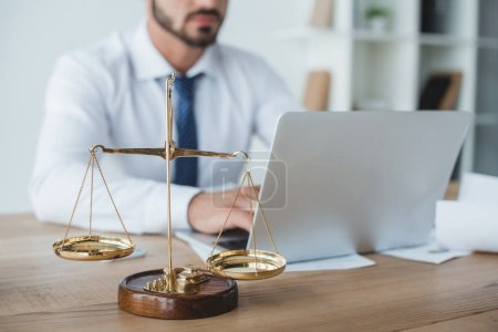 cropped image of business adviser working with laptop in office with scales on foreground