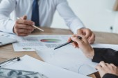 cropped image of business advisers pointing on documents at table in office