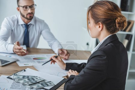 financiers pointing on documents at table in office