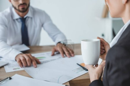 cropped image of business advisers working at table in office