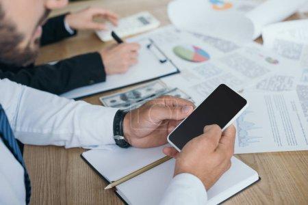 Photo pour Image recadrée d'un financier utilisant un smartphone au bureau - image libre de droit