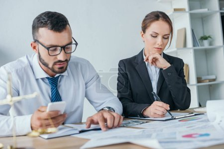 accountants working with documents and using smartphone in office