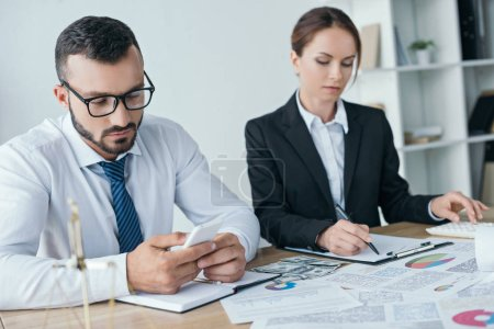 financiers working with documents and using smartphone in office