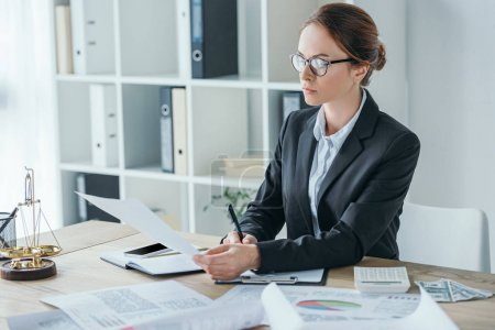 attractive financier working with documents at table in office