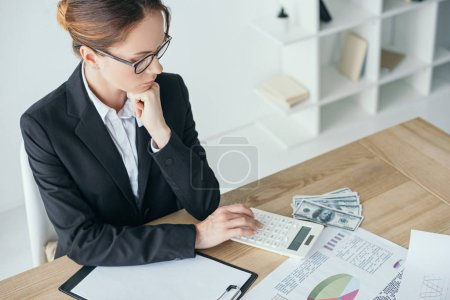 high angle view of financier working at table in office and using calculator