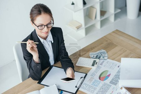 high angle view of financier working at table in office and using smartphone