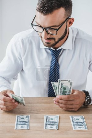 handsome business adviser in glasses counting dollar banknotes on table in office