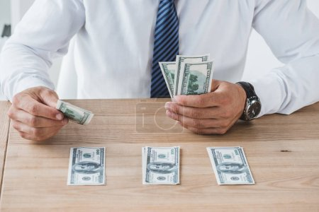 cropped image of business adviser counting dollar banknotes on table in office