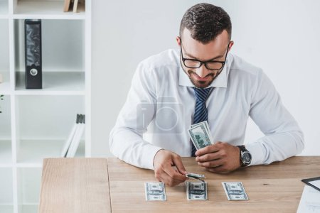 handsome financier counting dollar banknotes on table in office