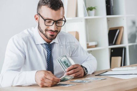 handsome business adviser counting dollar banknotes on table in office