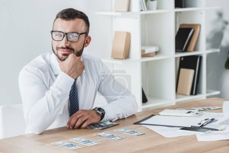 smiling business adviser sitting at table with dollar banknotes in office