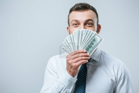 happy financier looking out from dollar banknotes isolated on grey
