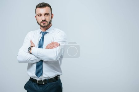 handsome businessman standing with crossed arms isolated on grey