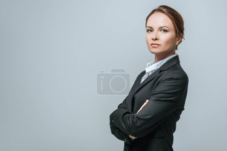 businesswoman standing with crossed arms isolated on grey