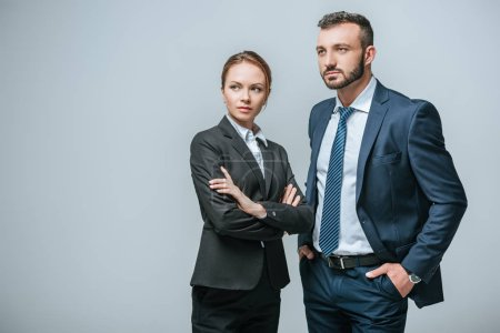 serious businesswoman and businessman looking away isolated on grey