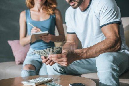 Photo pour Image recadrée de couple planification de budget familial et de compter l'argent dans le salon - image libre de droit
